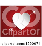 Cupids Arrow Through A White Paper Heart On Red