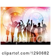 Clipart Of A Group Of Young Silhouetted Dancers Against Colorful Flares Sparkles And Lights Royalty Free Vector Illustration