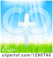 Sun Rays Shining Down On A White Cross With Easter Text Blue Sky And Green Grass