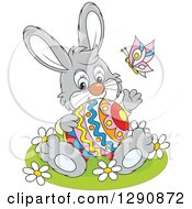 Clipart Of A Happy Cartoon Gray Bunny Rabbit Holding An Easter Egg And Waving Royalty Free Vector Illustration by Alex Bannykh