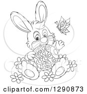 Clipart Of A Happy Cartoon Black And White Bunny Rabbit Holding An Easter Egg And Waving Royalty Free Vector Illustration