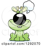 Clipart Of A Cartoon Happy Dreaming Or Thinking Green Jackalope Sitting Royalty Free Vector Illustration