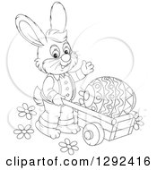 Clipart Of A Happy Black And White Easter Bunny Pushing A Giant Egg In A Wheelbarrow And Waving Royalty Free Vector Illustration