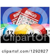 Clipart Of 3d Colorful Bingo Balls And Giant Cards With Blue Rays Over A Silhouetted Cheering Crowd Royalty Free Vector Illustration