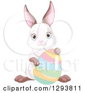 Clipart Of A Cute Easter Bunny Posing With A Colorful Easter Egg Royalty Free Vector Illustration