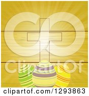 Clipart Of A Wood Panel And Ray Background With An Easter Cross And Striped Easter Eggs Royalty Free Vector Illustration by elaineitalia