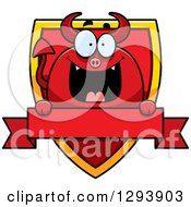 Clipart Of A Badge Or Label Of A Happy Devil Over A Shield And Blank Banner Royalty Free Vector Illustration