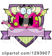 Clipart Of A Badge Or Label Of A Happy Dragon Over A Shield And Blank Banner Royalty Free Vector Illustration by Cory Thoman