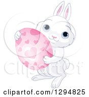 Clipart Of A Cute White Bunny Holding A Pink Heart Patterned Easter Egg Royalty Free Vector Illustration