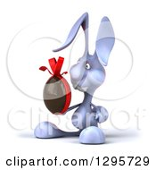 Clipart Of A 3d Blue Bunny Rabbit Facing Slightly Left And Holding A Chocolate Easter Egg Royalty Free Illustration