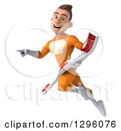 Clipart Of A 3d Young Brunette White Male Super Hero Dentist In An Orange Suit Facing Left Flying Pointing And Holding A Giant Toothbrush Royalty Free Illustration
