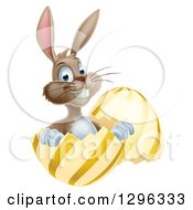 Clipart Of A Happy Brown Easter Bunny Sitting And Pointing In A Gold And Yellow Egg Shell Royalty Free Vector Illustration by AtStockIllustration