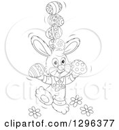 Clipart Of A Cartoon Black And White Easter Bunny Rabbit Balancing Eggs Royalty Free Vector Illustration
