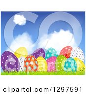 Clipart Of A 3d Colorful Shiny Patterned Easter Eggs In Grass Under A Blue Sky With Clouds Royalty Free Vector Illustration