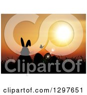 Clipart Of A Silhouetted Easter Bunny With Eggs A Butterfly And Grass Against An Orange Sunset Royalty Free Vector Illustration