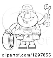 Clipart Of A Cartoon Black And White Male Mechanic Wearing A Tool Belt Waving With A Wrench And Standing With A Tire Royalty Free Vector Illustration
