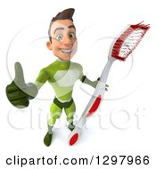 Clipart Of A 3d Young Brunette White Male Super Hero In A Green Suit Holding Up A Thumb And A Giant Toothbrush Royalty Free Illustration