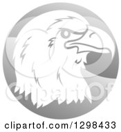 Clipart Of A Profiled Bald Eagle Or Falcon Head On A Shiny Gray Circle Royalty Free Vector Illustration