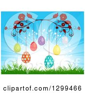 Clipart Of A Red Floral Vine With Suspended Patterned Easter Eggs Over Grass And A Sun Burst Royalty Free Vector Illustration