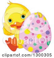 Clipart Of A Cute Yellow Duck Giving A Thumb Up And Sitting With An Easter Egg Royalty Free Vector Illustration