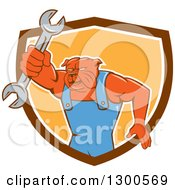 Clipart Of A Cartoon Bulldog Mechanic Holding Out A Wrench And Emerging From A Brown White And Orange Shield Royalty Free Vector Illustration