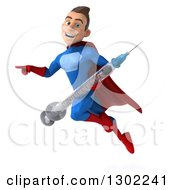 Clipart Of A 3d Young Brunette White Male Super Hero In A Blue And Red Suit Flying Pointing And Holding A Giant Syringe Royalty Free Illustration