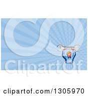 Clipart Of A Retro Low Poly Male Mechanic Holding Up A Spanner Wrench And Blue Rays Background Or Business Card Design Royalty Free Illustration