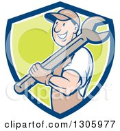 Clipart Of A Retro Cartoon Happy White Male Mechanic Holding A Giant Wrench Over His Shoulder And Emerging From A Blue White And Green Shield Royalty Free Vector Illustration