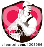 Clipart Of A Retro Male House Painter Holding A Brush And Bucket Looking Back In A Black And Pink Shield Royalty Free Vector Illustration
