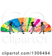Clipart Of Silhouetted Playful Children Over An Arch Of Colorful Rays And Stars Royalty Free Vector Illustration