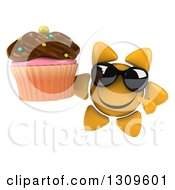 Clipart Of A 3d Happy Sun Character Wearing Sunglasses Holding And Pointing To A Chocolate Frosted Cupcake Royalty Free Illustration