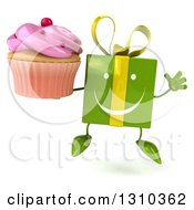 Clipart Of A 3d Happy Green Gift Character Jumping And Holding A Pink Frosted Cupcake Royalty Free Illustration