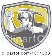 Clipart Of A Retro Male Coal Miner Holding Up A Fist And A Pickaxe In A Gray White And Green Shield Royalty Free Vector Illustration by patrimonio