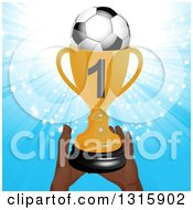 Pair Of Hands Holding Up A Golden First Place Championship Trophy With A Soccer Ball Over A Blue Star Burst