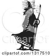 Clipart Of A Black And White Woodcut Wizard Standing With A Staff In A Breeze Royalty Free Vector Illustration