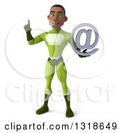 Clipart Of A 3d Young Black Male Super Hero In A Green Suit Holding Up A Finger And An Email Arobase At Symbol Royalty Free Illustration