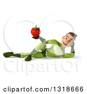 Clipart Of A 3d Young White Male Super Hero In A Green Suit Resting On His Side And Holding A Strawberry Royalty Free Illustration