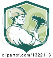 Clipart Of A Retro Male Construction Worker Holding A Sledgehammer In A Green And White Shield Royalty Free Vector Illustration