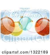 Clipart Of A Merry Christmas Greeting With Transparent Baubles On Blue With Snow Royalty Free Vector Illustration