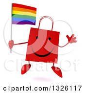 Clipart Of A 3d Happy Red Shopping Or Gift Bag Character Holding A Rainbow Flag And Jumping Royalty Free Illustration
