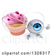 Clipart Of A 3d Blue Eyeball Character Holding Up A Thumb And A Pink Frosted Cupcake Royalty Free Illustration