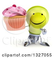 Clipart Of A 3d Happy Yellow Light Bulb Character Holding And Pointing To A Pink Frosted Cupcake Royalty Free Illustration