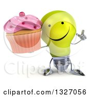 Clipart Of A 3d Happy Yellow Light Bulb Character Holding Up A Finger And A Pink Frosted Cupcake Royalty Free Illustration