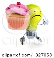 Clipart Of A 3d Unhappy Yellow Light Bulb Character Facing Slightly Right Jumping And Holding A Pink Frosted Cupcake Royalty Free Illustration