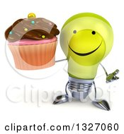 Clipart Of A 3d Happy Yellow Light Bulb Character Shrugging And Holding A Chocolate Frosted Cupcake Royalty Free Illustration