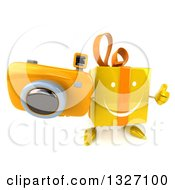 Clipart Of A 3d Yellow Gift Character Holding Up A Thumb And Camera Royalty Free Illustration by Julos