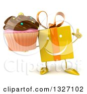 Clipart Of A 3d Happy Yellow Gift Character Holding Up A Finger And A Chocolate Frosted Cupcake Royalty Free Illustration by Julos