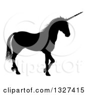 Clipart Of A Black Silhouetted Unicorn In Profile Walking To The Right Royalty Free Vector Illustration by AtStockIllustration