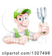 Clipart Of A Middle Aged Brunette White Male Gardener In Green Holding Up A Garden Fork And Pointing Royalty Free Vector Illustration