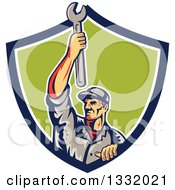 Clipart Of A Retro Male Mechanic Holding A Wrench Above His Head In A Blue White And Green Shield Royalty Free Vector Illustration